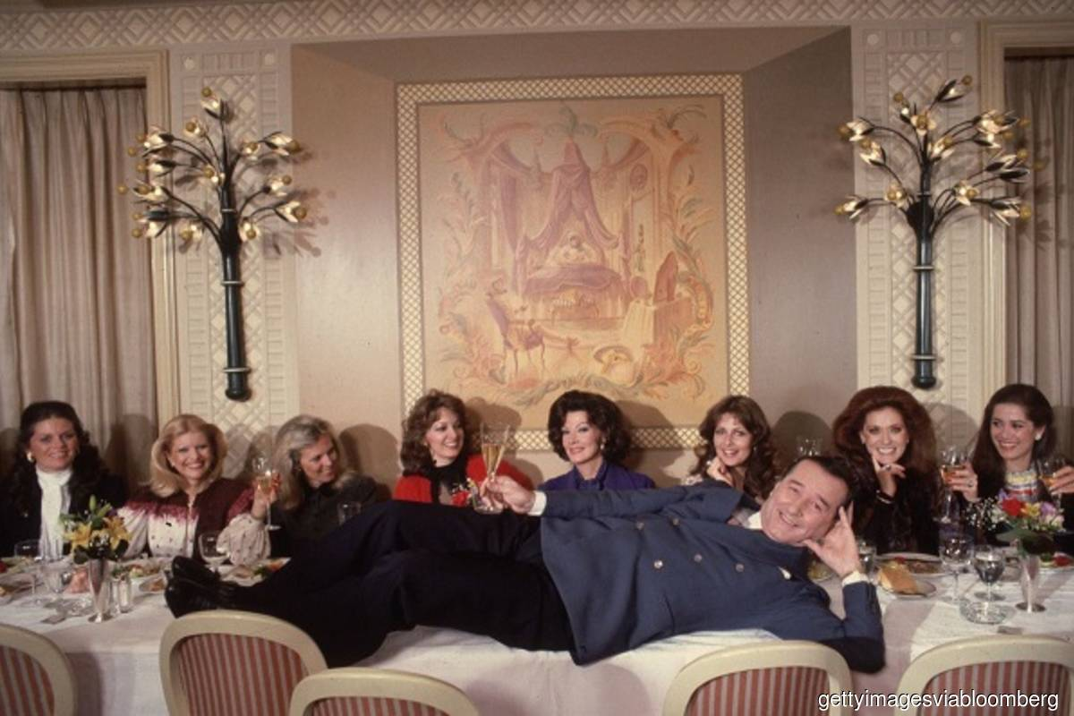 The late Sirio Maccioni hams it up in a 1981 photo with ladies who lunched. (From left: Kathryn Penske, Ivana Trump, Muffie Bancroft, Anne Arledge, Anna Moffo Sarnoff, Cristina DeLorean, Maria Kimberly, and Patricia Kluge.) (Photo credit: Slim Aarons/Getty Images via Bloomberg)