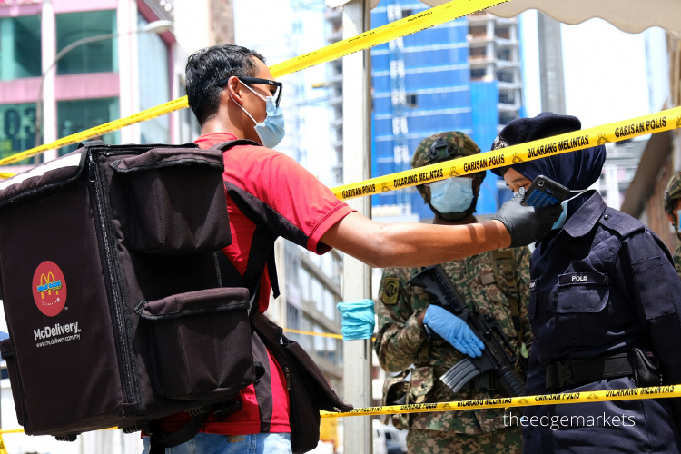 A food delivery worker speaking to police officers outside Menara One City at Jalan Munshi Abdullah, which has been placed under the Enhanced Movement Control Order (EMCO) since March 31. (Photographer: Suhaimi Mohd Yusuf/The Edge)