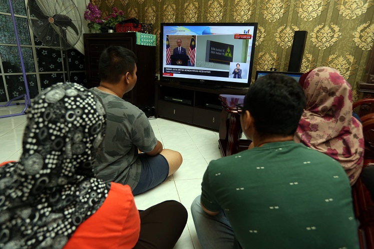 A family watching Prime Minister Tan Sri Muhyiddin Yassin announcing the second stimulus package on television. (Photo by Mohd Suhaimi Mohamed Yusuf/The Edge)