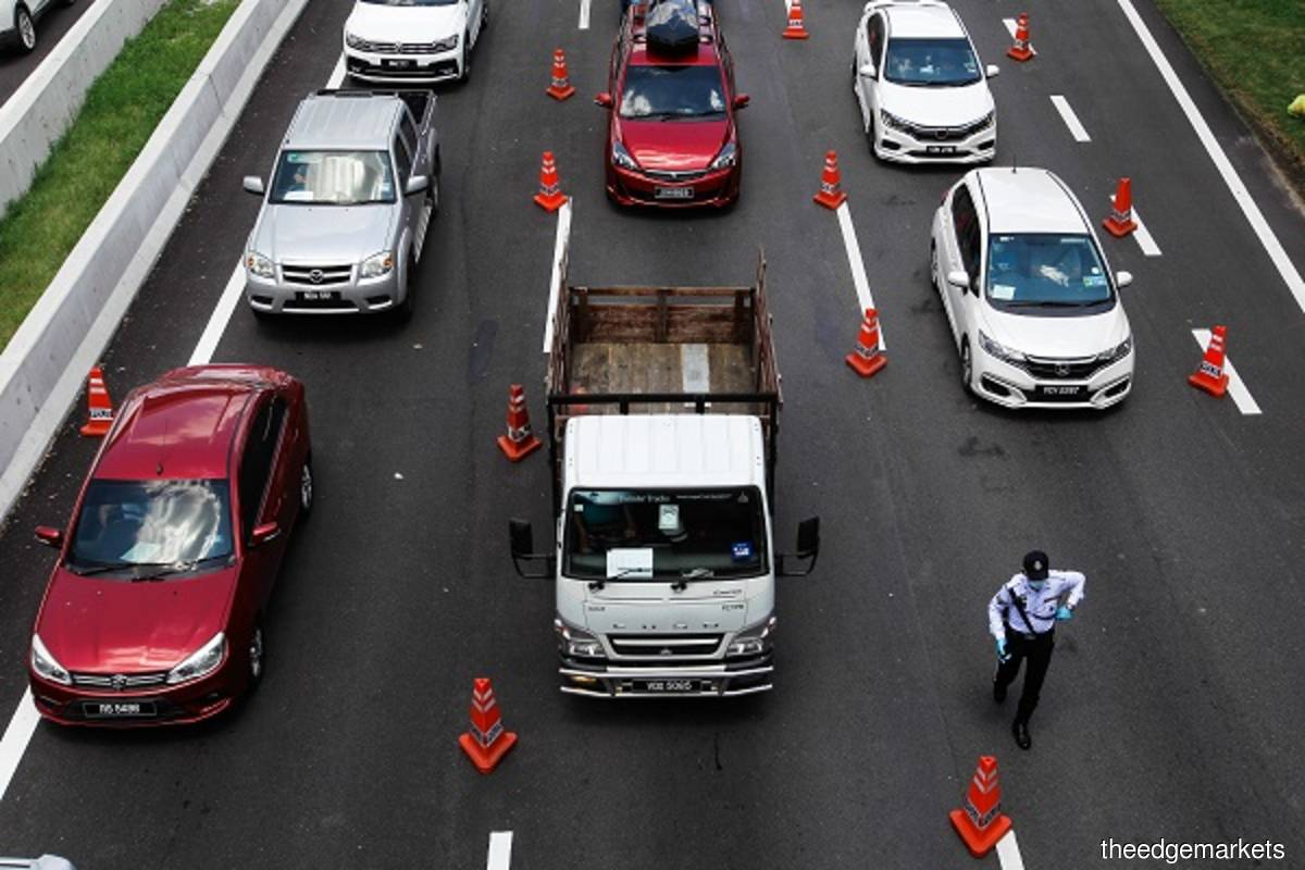 Police set up roadblocks at the Sg.BesI Toll Plaza exit for all vehicles entering Kuala Lumpur by checking their cross-state permission letters on Monday May 10, 2021. (Photo by Zahid Izzani/The Edge)