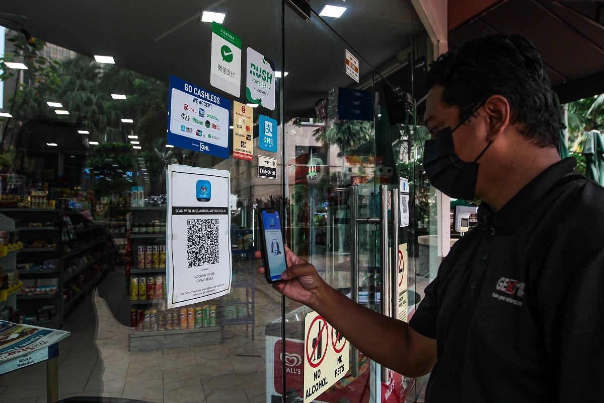 A man seen using the MySejahtera app to scan a QR code before entering a store yesterday (Aug 3). The nation's cumulative Covid-19 cases increased further to 1.18 million today from just 758,967 as of July 1. (Photo by Zahid Izzani Mohd Said/The Edge)