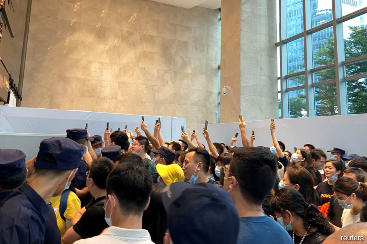 People gather to demand repayment of loans and financial products as security personnel guard outside Evergrande's headquarters in Shenzhen, Guangdong province, China.