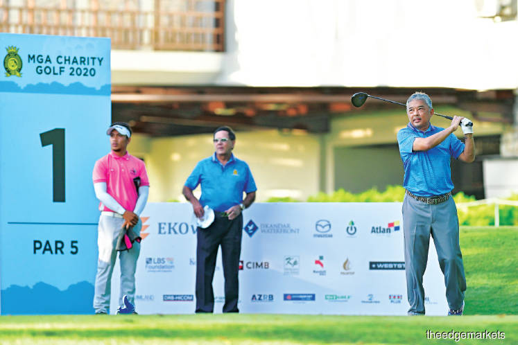 Al-Sultan Abdullah (right) teeing off at the first hole of the MGA Charity Golf tournament at the Kota Permai Golf and Country Club in Shah Alam, Selangor yesterday.