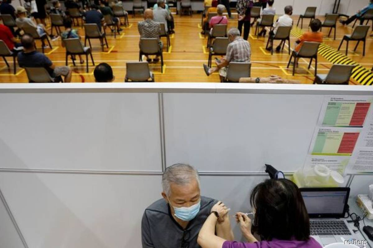 A man receives his vaccination at a coronavirus disease (Covid-19) vaccination centre in Singapore on March 8, 2021. (Photo by Edgar Su/Reuters filepix)
