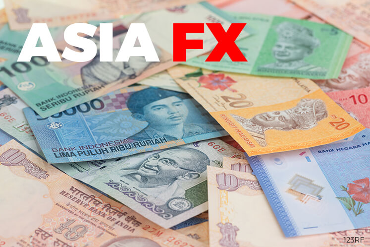Asian currencies inch lower, focus on US healthcare vote