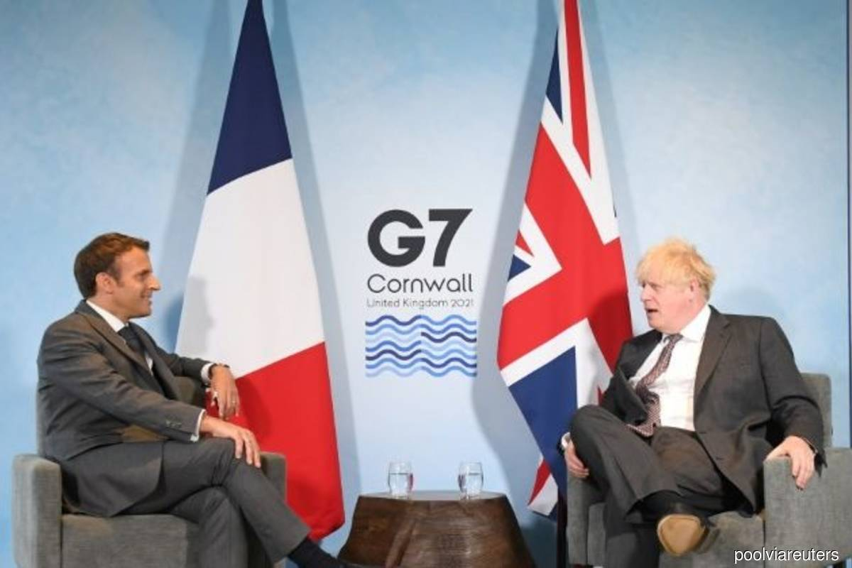 Britain's Prime Minister Boris Johnson and France's President Emmanuel Macron attend a bilateral meeting during G7 summit in Carbis Bay, Cornwall, Britain, on Saturday June 12, 2021. (Photo credit: Stefan Rousseau/Pool via Reuters)
