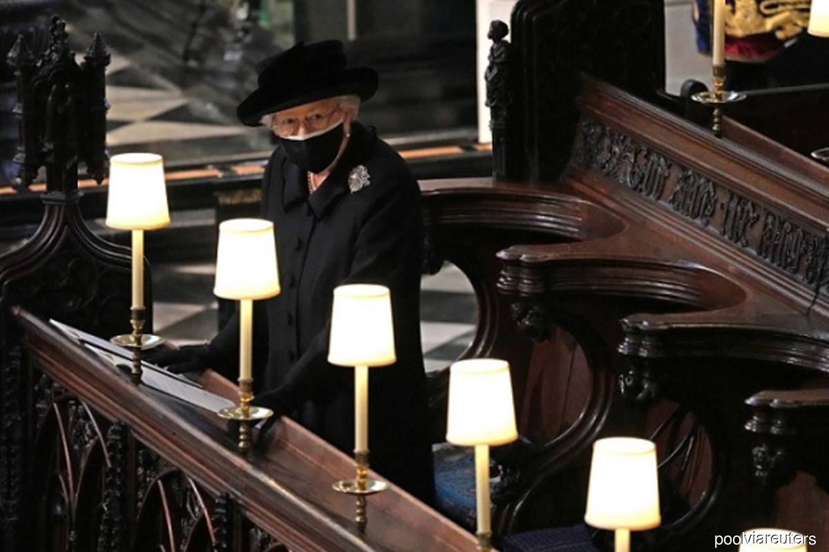 Queen Elizabeth stands alone as Philip is laid to rest; William and Harry talk