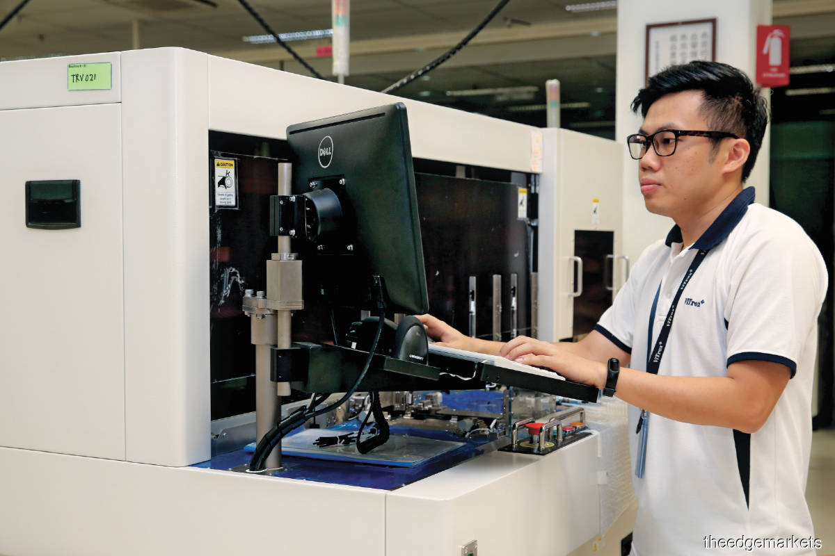 A ViTrox manufacturing engineer operating a semiconductor component inspection handler. (Photo by Sam Fong/The Edge)