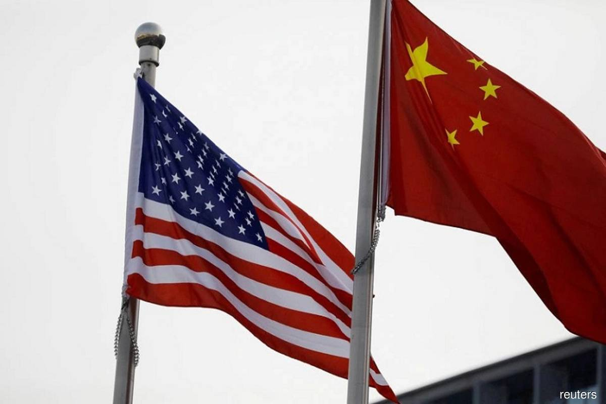 Chinese and US flags flutter outside the building of an American company in Beijing, China on Jan 21, 2021. (Photo by Tingshu Wang/Reuters filepix)