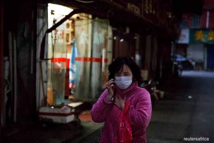 A woman wears a face mask in a market alley in Jiujiang, Jiangxi province, China on Feb 1, 2020, as the country is hit by an outbreak of a new coronavirus. (Photo credits: Thomas Peter/REUTERS)