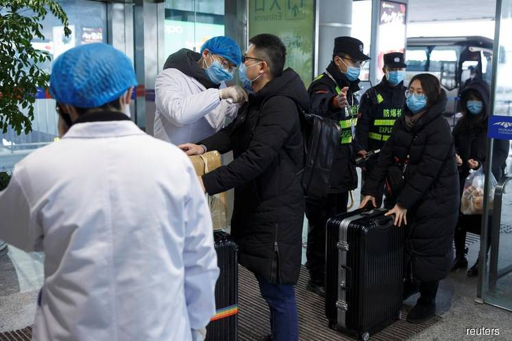 A medical official takes the body temperature of a man at the departure hall of the airport in Changsha, Hunan Province, China on  Jan 27, 2020, as the country is hit by an outbreak of a new coronavirus. (Photo by Thomas Peter/REUTERS)