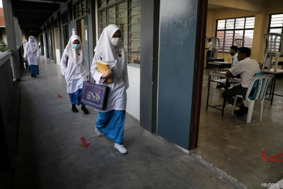 Illustration of secondary school students wearing masks, adhering to government Covid-19 prevention SOPs, as they walk to their classrooms in a school in Peninsula Malaysia on June 24, 2020 (Photo credit: Lim Huey Teng/Reuters filepix)