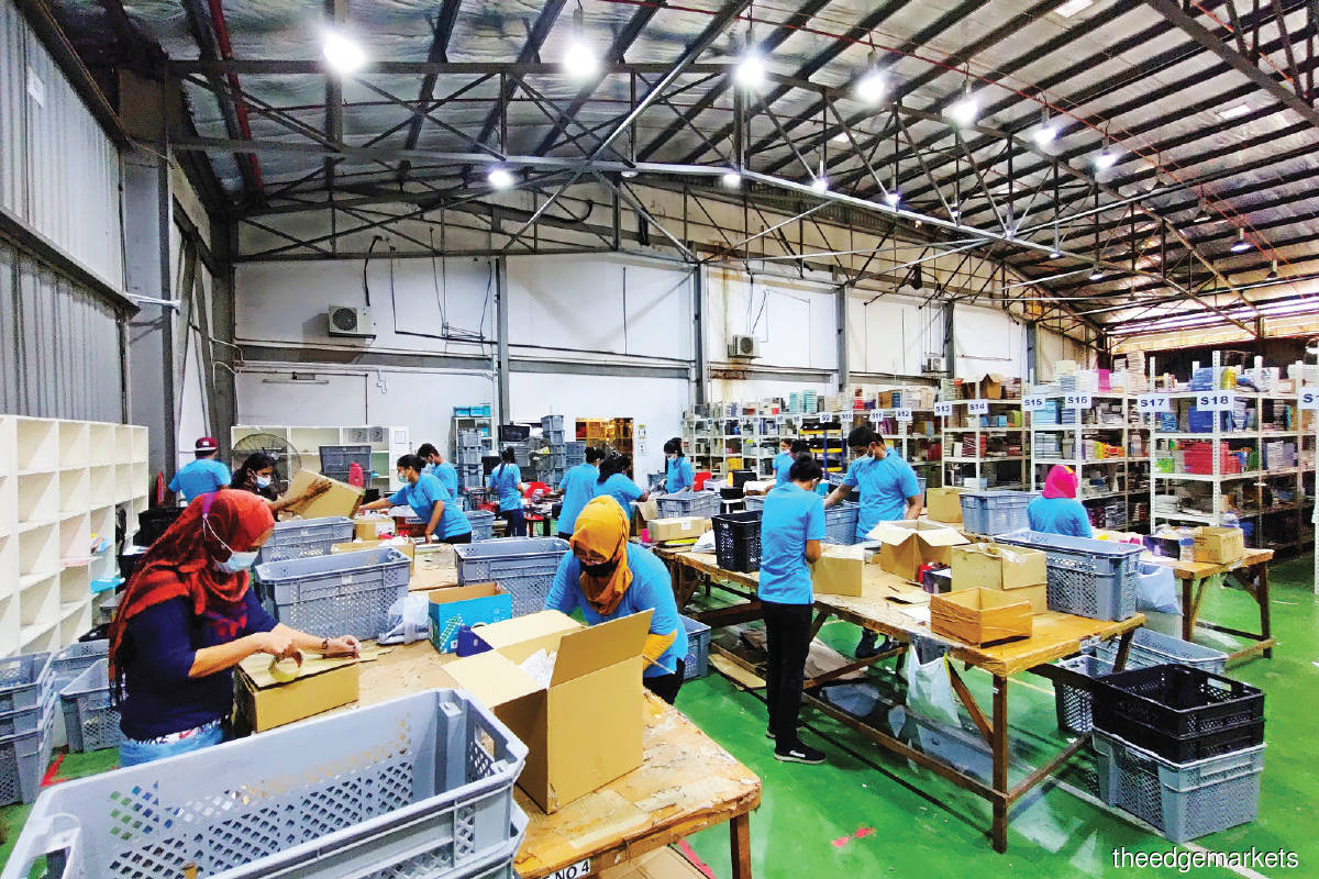 Workers fulfilling orders at the packing station. Behind them is the e-commerce shelving system.