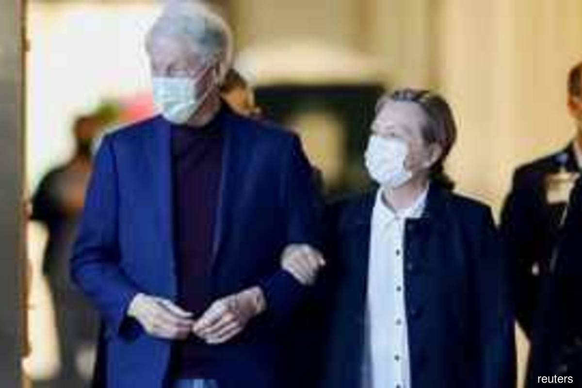 Former US President Bill Clinton, accompanied by his wife, former Secretary of State Hillary Clinton, walks out of University of California Irvine Medical Centre in US on Sunday Oct 17, 2021 (Photo by David Swanson/Reuters)