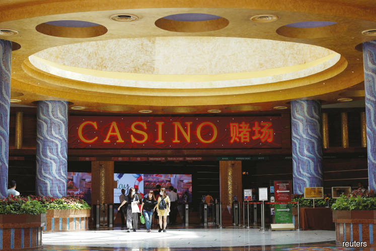 People wearing masks seen leaving the casino at Resorts World Sentosa in Singapore. The Singapore government announced on Sunday that except those providing essential services, most businesses must cease operations from today to May 4. (Photo by Reuters)