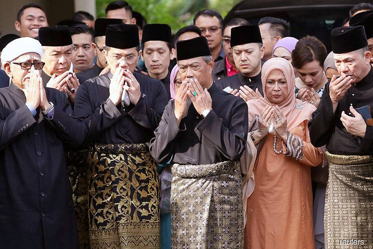 Muhyiddin (centre) praying with his supporters before his inauguration as the eighth prime minister outside his residence in Kuala Lumpur on March 1. (Photo by Reuters)