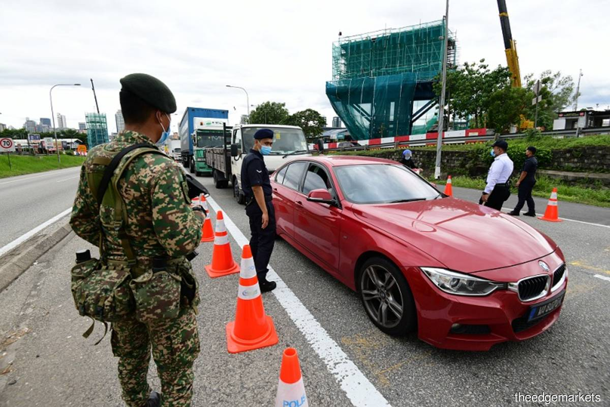 Police inspect vehicles at mounted roadblock at a Klang Valley vicinity on day 1 of MCO 2 operations today. (Photo credit: Patrick Goh/theedgemarkets)