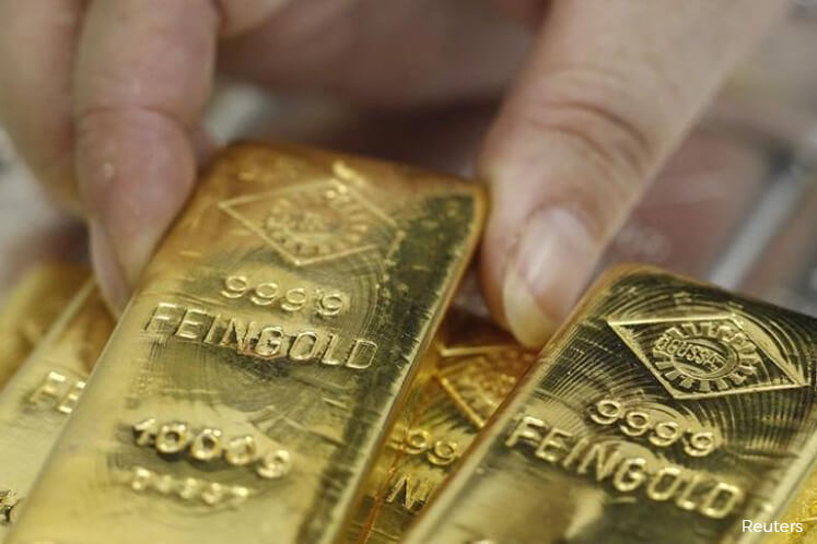 Gold heads for 1st weekly gain in three as Fed hurts dollar