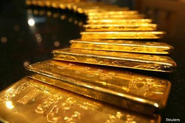 Gold slips on firmer US dollar; political uncertainty supports