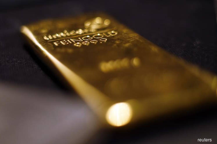 Gold rises as dollar slips, en route first weekly gain in three