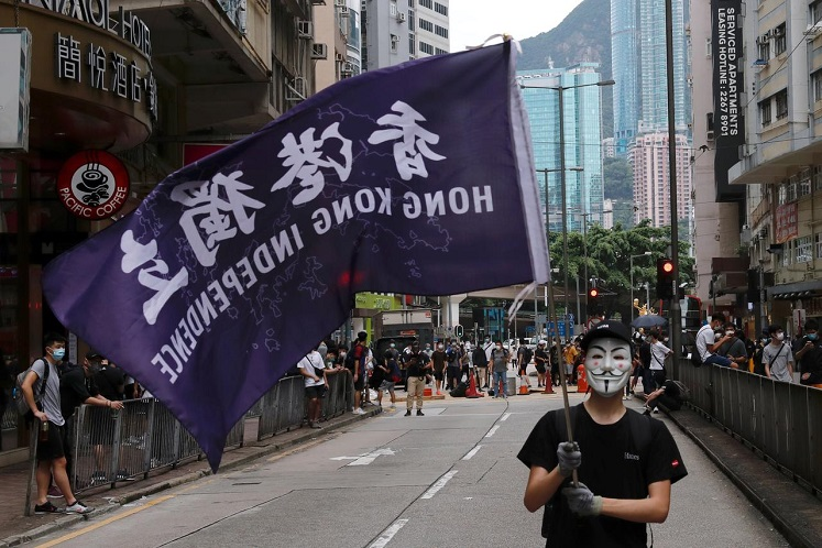 A masked anti-government protester holds a flag supporting Hong Kong independence during a march against Beijing's plans to impose national security legislation in Hong Kong, China May 24, 2020. (Photo by Reuters)