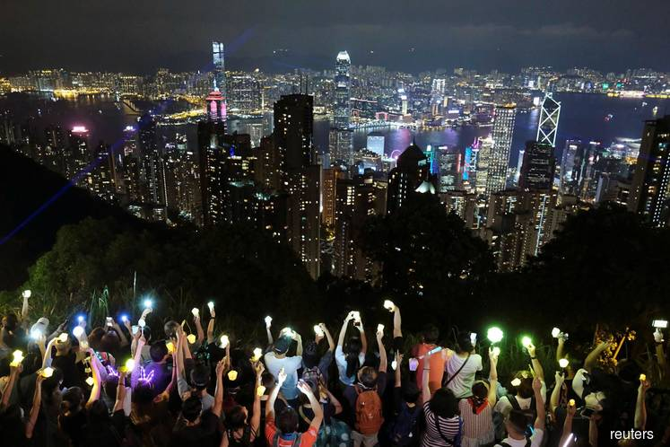 Lantern-waving Hong Kong protesters take to hills, as leader pledges housing reform