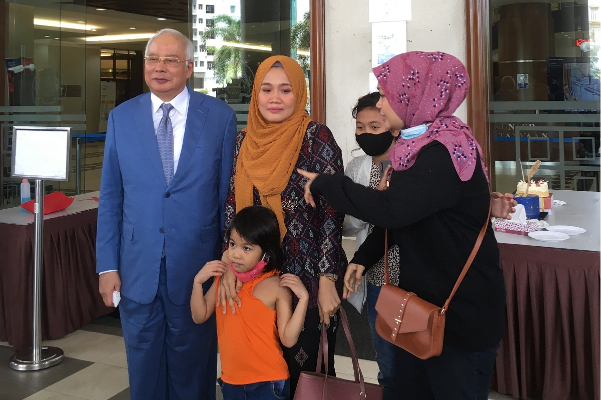Najib celebrated his 67th birthday with his supporters, who surprised him with two cakes at the Kuala Lumpur Court Complex on July 23. One of the cakes can be seen on the table behind Najib and his supporters. (Photo by Emir Zainul)