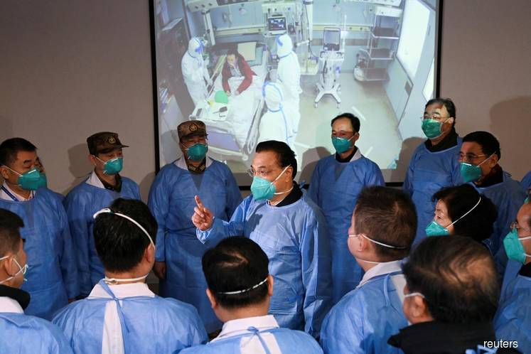 Chinese Premier Li Keqiang wearing a mask and protective suit speaks to medical workers as he visits the Jinyintan hospital where the patients of the new coronavirus are being treated following the outbreak, in Wuhan, Hubei province, China, January 27, 2020. (cnsphoto via Reuters)