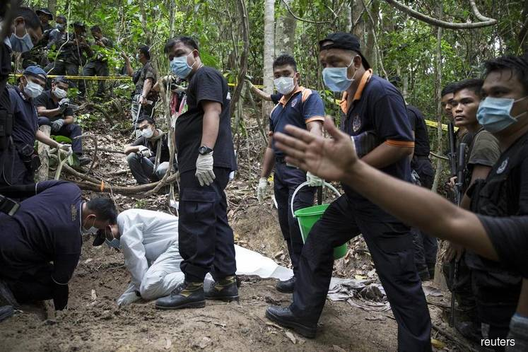 Malaysia begins inquiry into 2015 discovery of mass graves, human trafficking camps