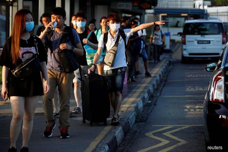 Bags packed, Malaysians stream into Singapore ahead of coronavirus travel ban