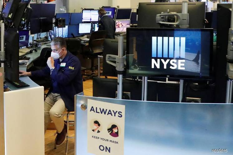 Wall St falls as Fed action hits bank stocks, virus cases surge