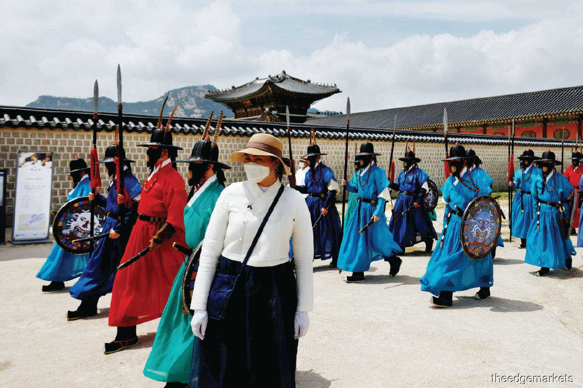 A woman standing next to workers wearing traditional dress during the daily re-enactment of the changing of the Royal Guards at Gyeongbok Palace in Seoul ... South Korea has remained diligent in preventing the spread of Covid-19. (Photo Reuters)