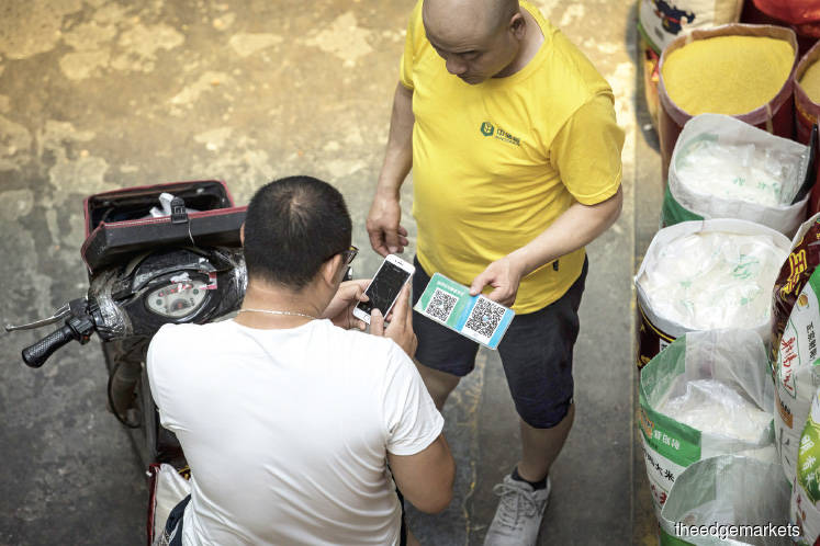 A customer scanning the QR code of a grain store to pay at a wholesale market in Shanghai, China