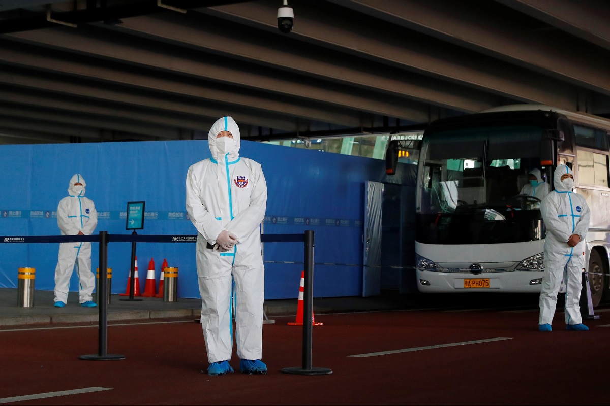 Staff members in protective suits stand guard next to a bus before the expected arrival of a WHO team tasked with investigating the origins of the Covid-19 pandemic, at Wuhan Tianhe International Airport in Wuhan, Hubei province, China, Jan 14, 2021. (Photo by Reuters)