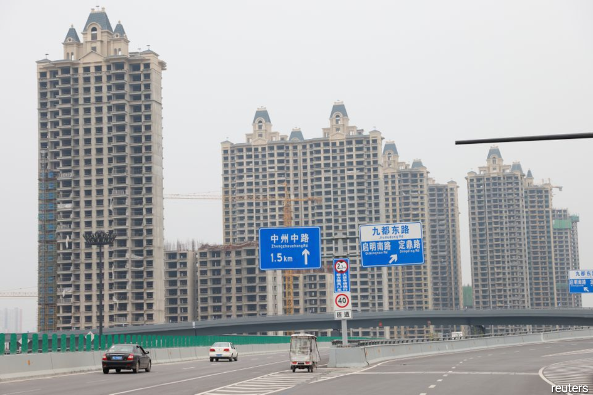 A vehicle drives past unfinished residential buildings at Evergrande Oasis, a housing complex developed by Evergrande Group, in Luoyang, China September 16, 2021.