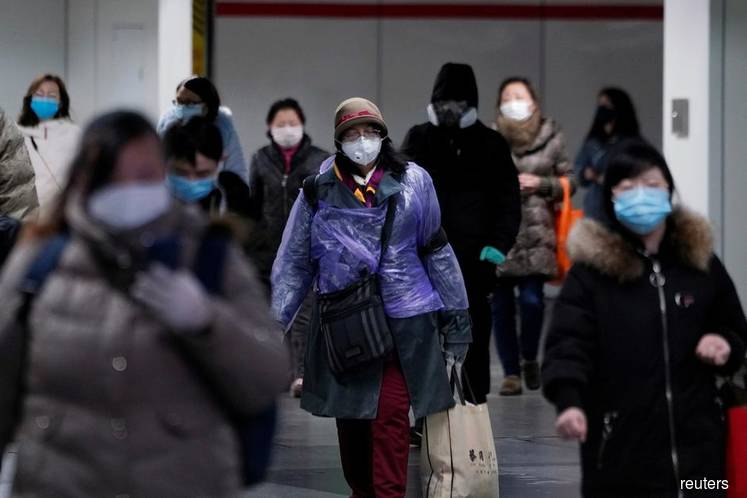 People wearing face masks walk inside a subway station on Monday Feb 17, 2020 in Shanghai, China, as the country is hit by an outbreak of the 2019 novel coronavirus (Covid-19). (Photo caption: Aly Song/REUTERS)