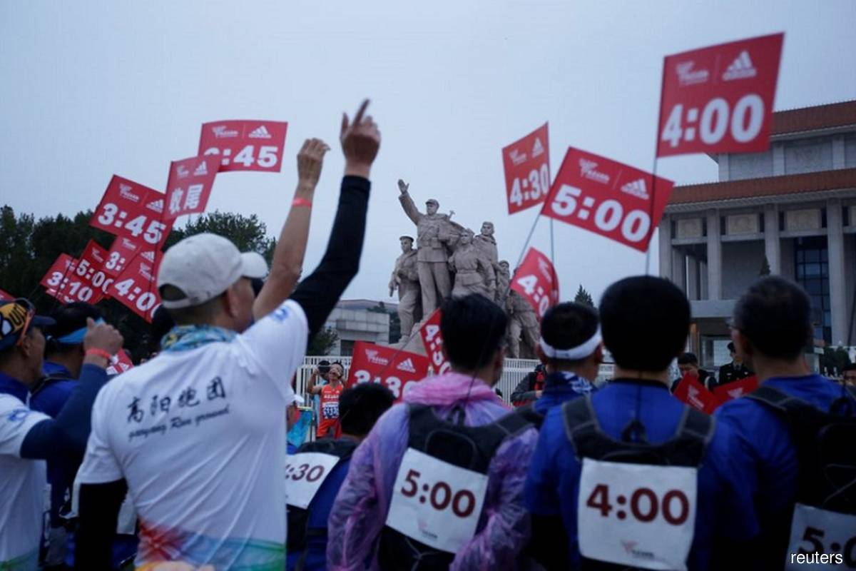 Staff members gather at Tiananmen Square before the start of the annual Beijing Marathon in Beijing, China on Nov 3, 2019. (Photo by Jason Lee/Reuters filepix)