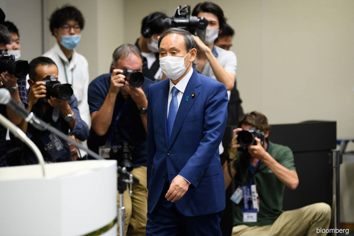 Japan's Suga praises democracy in party vote stacked for him