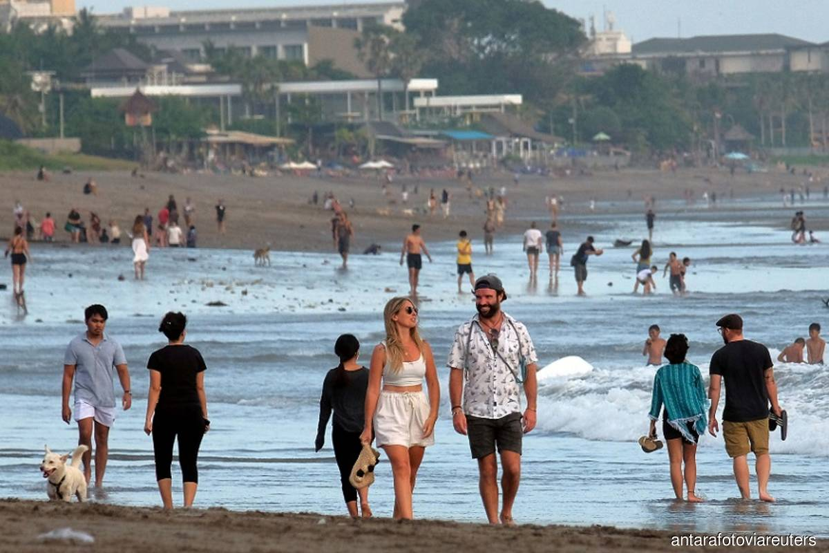 Tourists walk on a beach as the government extends restrictions to curb the spread of coronavirus disease (Covid-19) in Badung, Bali, Indonesia on Sept 9, 2021. (Photo by Nyoman Hendra Wibowo/Antara Foto via Reuters)