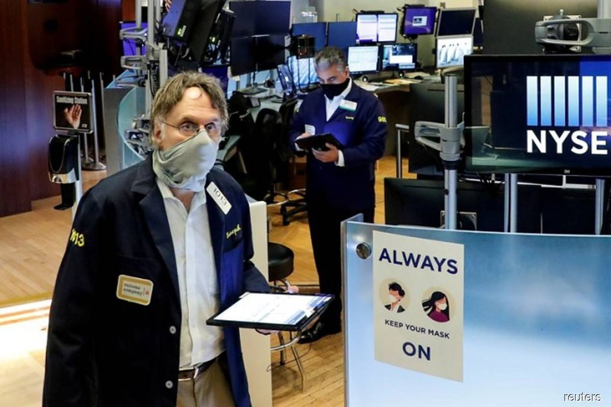Traders wearing masks work, on the first day of in person trading since the closure during the outbreak of the coronavirus disease (Covid-19), on the floor at the New York Stock Exchange (NYSE) in New York, US on May 26, 2020. (Photo by Brendan McDermid/Reuters filepix)