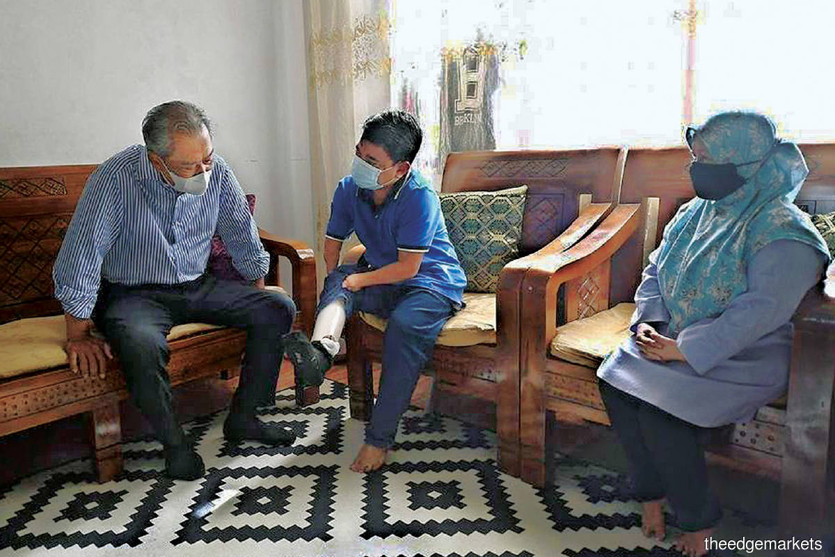 Muhyiddin (left) listening to Desa Rejang PPR resident Rosali (centre) during his visit on Aug 25. (Photo by Muhyiddin's facebook)