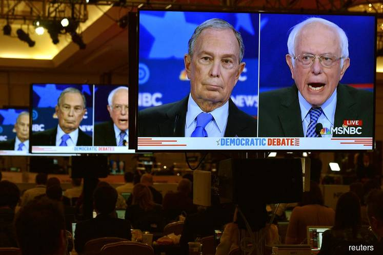 FILE PHOTO: Former New York City Mayor Mike Bloomberg and Senator Bernie Sanders are seen on video screens in the media filing centre during the ninth Democratic 2020 U.S. Presidential candidates debate at the Paris Theater in Las Vegas, Nevada, U.S. on Wednesday Feb 19, 2020. (Photo by: David Becker/REUTERS)