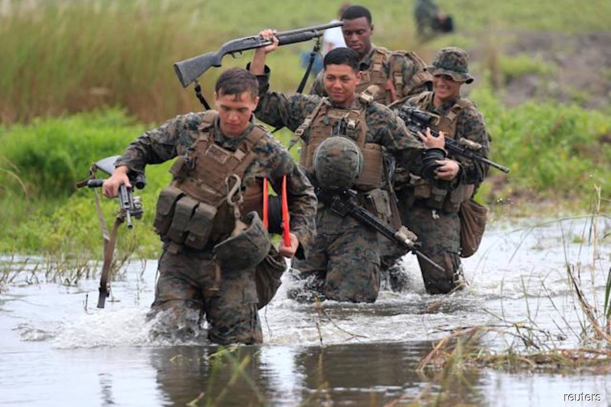 US military forces cross a flooded area near the shore during the annual Philippines-US amphibious landing exercise (PHIBLEX) at San Antonio, Zambales province, Philippines on Oct 7, 2016. (Photo credit: Romeo Ranoco/Reuters filepix)