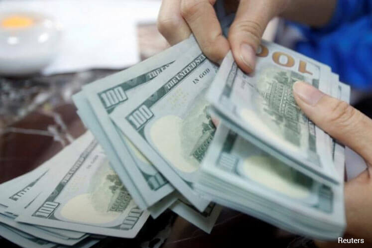 Dollar hovers near 22-month peak buoyed by strong U.S. data