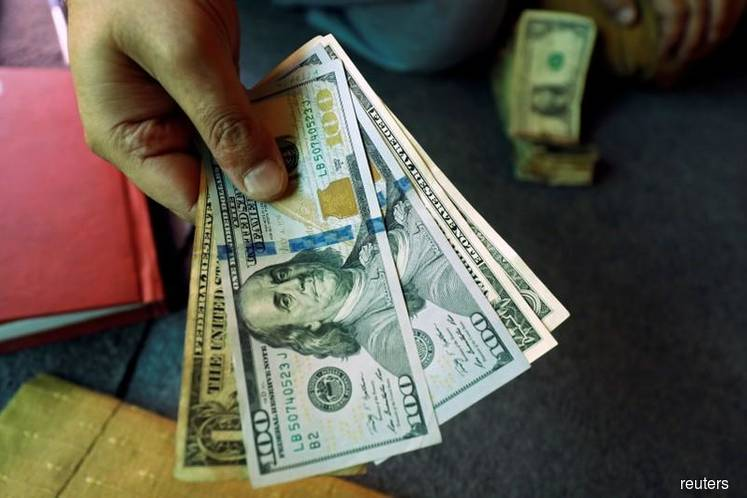 Dollar gains on trade deal hopes, strong U.S. economic data