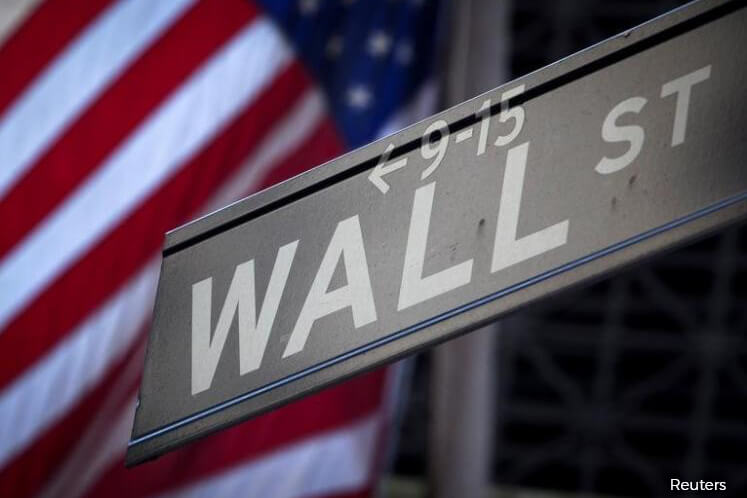 Wall St ends near flat; healthcare shares gain but trade deal delay weighs