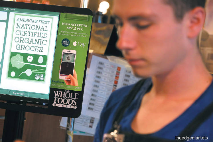 A sign announcing that Whole Foods accepts Apple Pay is posted on a cash register when the payment system was launched in 2014