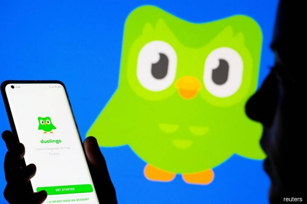 A woman with her smartphone poses in front of a displayed Duolingo logo in this illustration taken on June 29, 2021. (Photo by Dado Ruvic/Reuters illustration filepix)