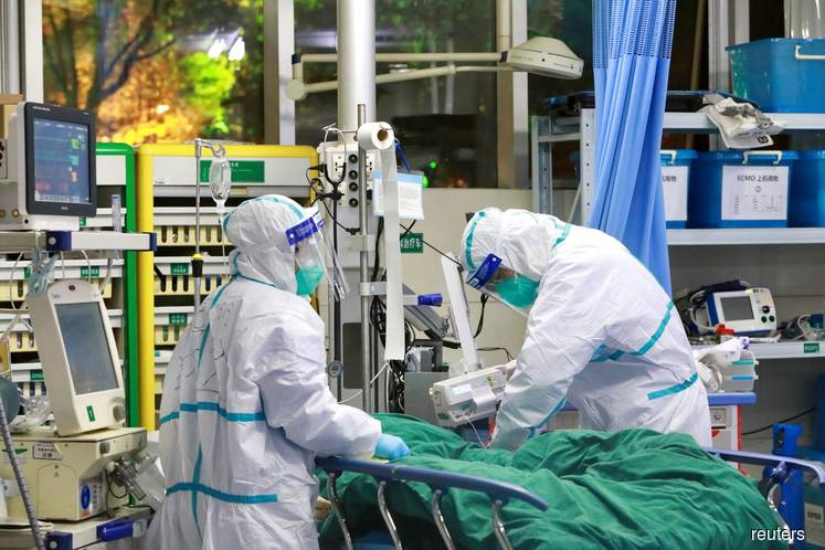 Medical staff in protective suits treat a patient with pneumonia caused by the new coronavirus at the Zhongnan Hospital of Wuhan University, in Wuhan, Hubei province, China on Jan 28, 2020. (Photo credit: China Daily via REUTERS)