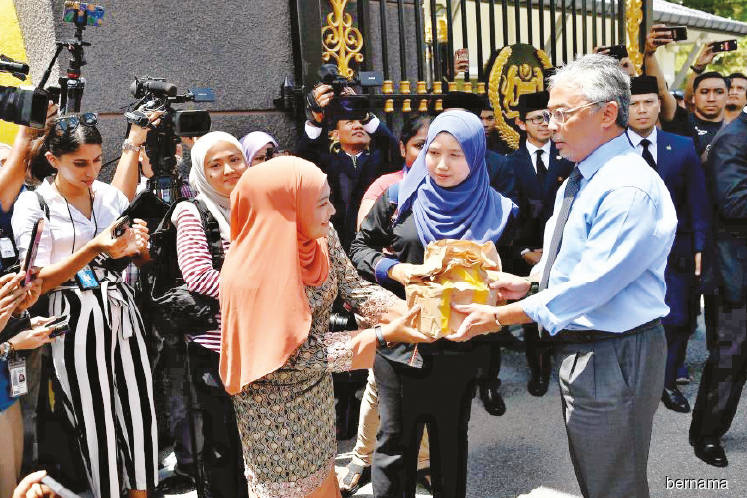 Al-Sultan Abdullah (right) distributing bags of food to surprised journalists camped at the entrance of Istana Negara in Kuala Lumpur during lunch time yesterday. (Photo by Bernama)